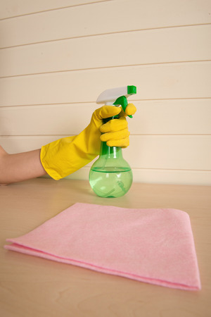 charlady: Water sprayer standing on the table near the pink duster Stock Photo