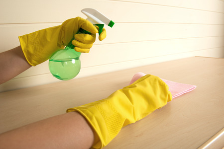 Housemaid wearing yellow gloves spraying water on the duster photo