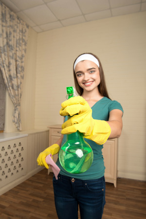 Selected focus on the water sprayer in the hand of beautiful smiling housemaid wearing nice shirt and jeans on background photo