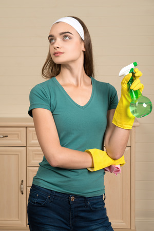 Half-length portrait of nice dark-haired housemaid wearing white fillet and holding water sprayer in one hand thinking about one more flat where she must clean photo