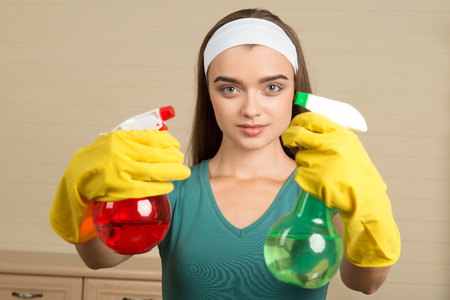 Half-length portrait of beautiful young housemaid wearing rubber yellow gloves showing us red water sprayer in one hand and green in another photo