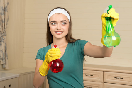 Half-length portrait of lovely smiling dark-haired housemaid wearing yellow rubber gloves and pulverizing water from the colorful water sprayers photo
