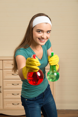 Half-length portrait of pretty young smiling housemaid wearing white fillet and yellow rubber gloves holding two colorful water sprayers  She is ready to clean photo