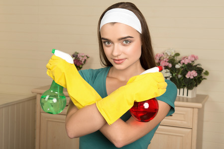 charlady: Half-length portrait of beautiful dark-haired housemaid wearing white fillet with crossed arms holding two colorful water sprayers and looking at us Stock Photo