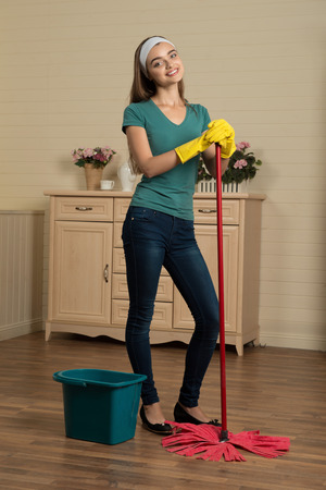 charlady: Full-length portrait of beautiful smiling housemaid wearing blue shirt and jeans standing in the room near the mop and pail