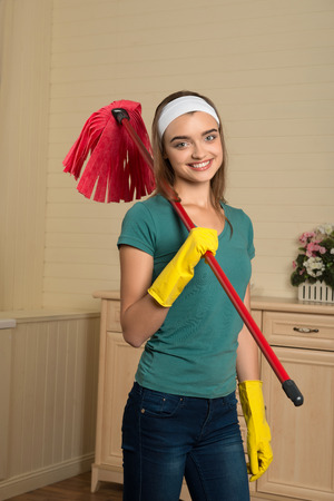 charlady: Half-length portrait of beautiful smiling housemaid wearing blue shirt and yellow rubber gloves holding red mop on her shoulder