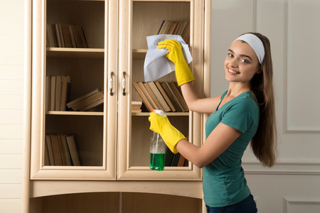 charlady: Half-length portrait of nice smiling dark-haired housemaid standing aside in white fillet dusting the book shelf and looking at us Stock Photo