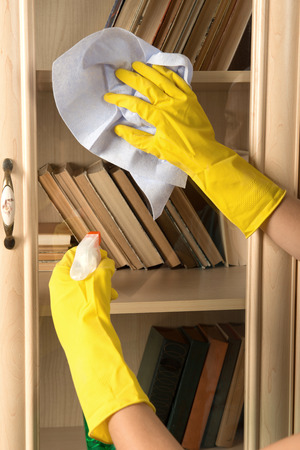 charlady: Woman wearing yellow rubber gloves dusting the book shelf