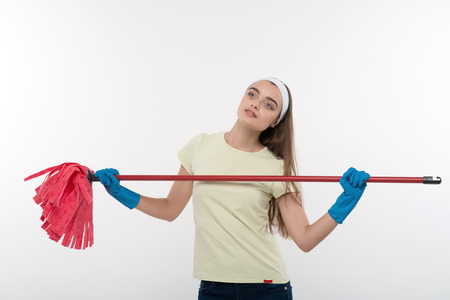 charlady: Half-length portrait of happy smiling housemaid wearing white shirt and blue rubber gloves taking pride in her new red mop  Isolated on white background