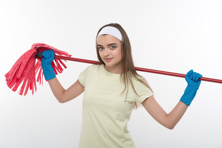 charlady: Half-length portrait of beautiful dark-haired housemaid wearing white shirt and blue rubber gloves holding the red mop on her shoulders  Isolated on white background Stock Photo