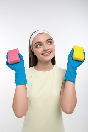 charlady: Half-length portrait of young smiling housemaid wearing nice white headband, satisfied with her new colorful washcloths  Isolated on white background Stock Photo