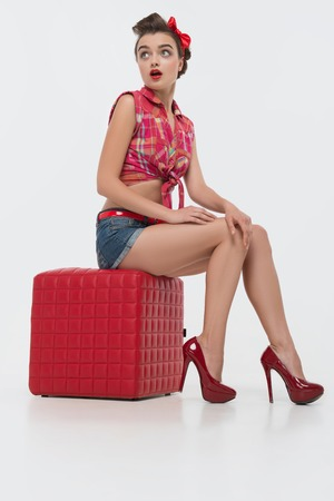 charlady: Glamorous young smiling maid wearing great red vest blue shorts and wonderful bootee sitting on the padded stool surprised with the appearance of her boss  Isolated on white background Stock Photo