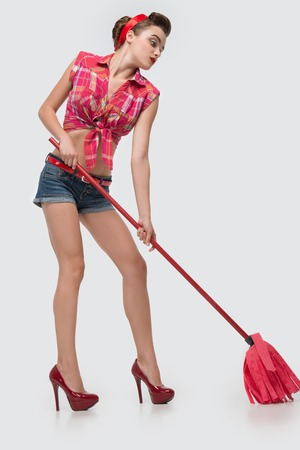 bootee: Glamorous young charming maid wearing great red vest blue shorts and wonderful bootee trying to scrub floors  Isolated on white background Stock Photo