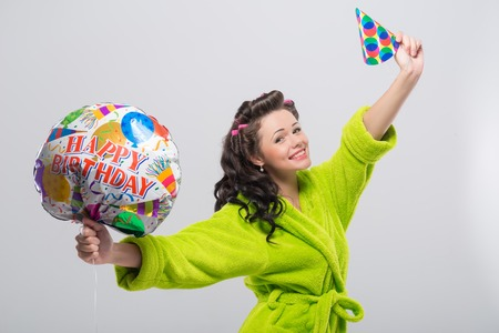 Half-length portrait of happy young housewife wearing curlers and green wrapper showing us wonderful colorful balloon and cap. photo