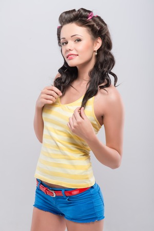 Half-length portrait of pretty young housewife wearing curlers nice yellow shirt and blue shorts smiling and looking at us. photo