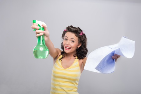 Half-length portrait of young smiling housewife wearing curlers nice yellow shirt and blue shorts showing the water spray and duster to us. photo
