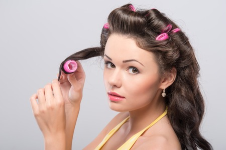 Beautiful young dark-haired woman wearing nice yellow shirt turning her hair on the pink curler   photo