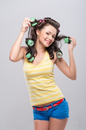 Half-length portrait of happy smiling young housewife wearing green curlers yellow shirt and blue shorts taking pride in her wonderful curly hair   photo