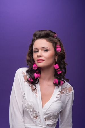 ardently: Half-length portrait of beautiful young woman wearing pink curlers and white satin dressing gown with nice make up looking at us