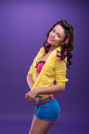 ardently: Half-length portrait of charming young smiling woman with curly hair nice pink bra blue shorts binding her yellow shirt standing aside to us looking ardently
