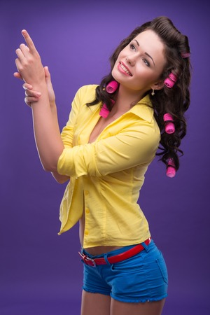 ardently: Half-length portrait of charming young smiling woman with curly hair nice yellow shirt and blue shorts pointing at something funny