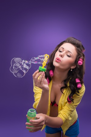 ardently: Half-length portrait of charming young smiling woman with curly hair wearing nice yellow shirt and pink curlers blowing the bubbles   Stock Photo