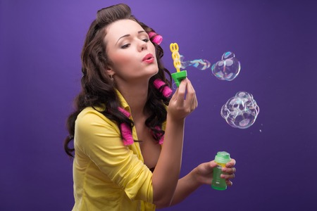 ardently: Half-length portrait of charming young smiling woman with curly hair wearing nice yellow shirt and pink curlers blowing the bubbles