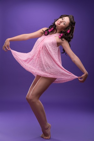 ardently: Half-length portrait of charming young smiling woman with curly hair wearing nice pink dress dancing like a princess   Stock Photo
