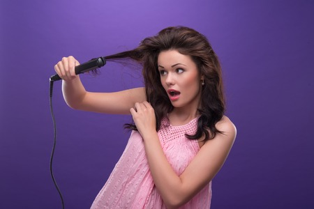 ardently: Half-length portrait of astonished young woman with curly hair wearing nice pink dress straightening her hair with the curling irons