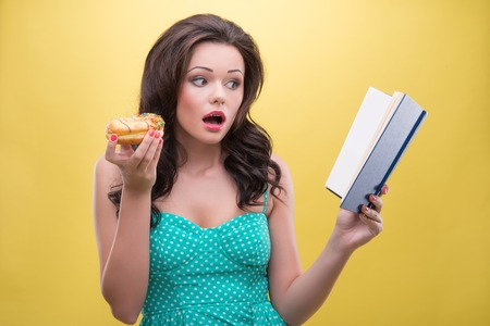 relishing: Half-length portrait of very beautiful dark-haired woman relishing her favorite sweet doughnut reading the interesting book  Isolated on yellow background