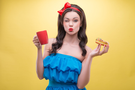 Half-length portrait of lovely dark-haired woman wearing nice red headband and wonderful blue dress kissed us holding tasty doughnut in one hand and aromatic coffee in another  Isolated on yellow background Stock Photo - 30719063