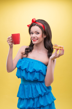 Half-length portrait of lovely dark-haired woman holding tasty doughnut in one hand and aromatic coffee in another and dreaming about her future wedding  Isolated on yellow background Stock Photo - 30745145