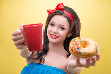 suggested: Half-length portrait of lovely smiling dark-haired woman wearing nice red headband and wonderful blue dress suggested us her aromatic coffee and tasty doughnut  Isolated on yellow background