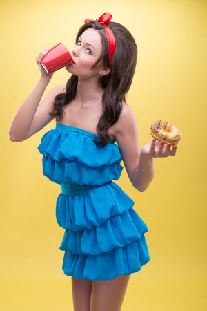 Half-length portrait of lovely smiling dark-haired woman wearing nice red headband and wonderful blue dress standing aside to us drinking her aromatic coffee and holding iced doughnut  Isolated on yellow background Stock Photo - 30745147