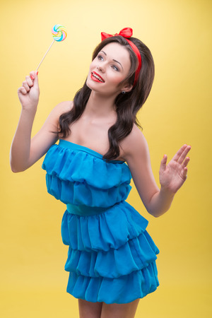 Half-length portrait of pretty smiling dark-haired woman wearing nice red headband and wonderful blue dress standing aside with her candy and dreaming about her date  Isolated on yellow background Stock Photo