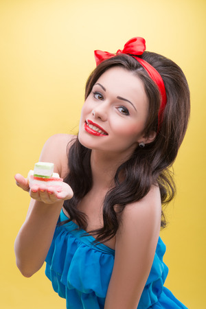 sugarplum: Half-length portrait of charming smiling dark-haired woman wearing nice red headband and wonderful blue dress holding on her palm very delicious colorful fruit drops  Isolated on yellow background