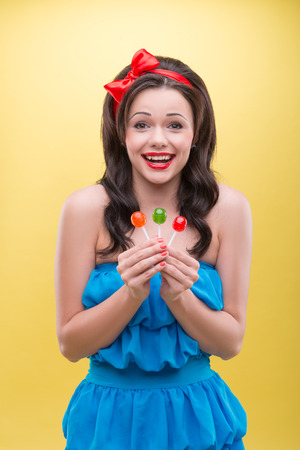 sugarplum: Half-length portrait of lovely smiling dark-haired woman wearing nice red headband and blue dress holding three sweet colorful bonbons  Isolated on yellow background Stock Photo