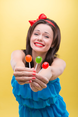Half-length portrait of lovely smiling dark-haired woman wearing nice red headband and blue dress presented us three sweet colorful bonbons  Isolated on yellow background Stock Photo - 30717491