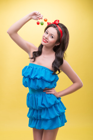 Half-length portrait of lovely smiling dark-haired woman wearing nice red headband and blue dress holding three sweet colorful bonbons near her head  Isolated on yellow background Stock Photo - 30717493