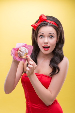 breaking off: Half-length portrait of very excited dark-haired woman wearing great red headband and dress breaking off piece of appetizing short cake  Isolated on yellow background Stock Photo