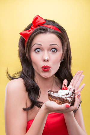 Half-length portrait of happy beautiful dark-haired woman wearing great red headband holding tasty chocolate cake and taking pleasure in her favorite dessert  Isolated on yellow background photo