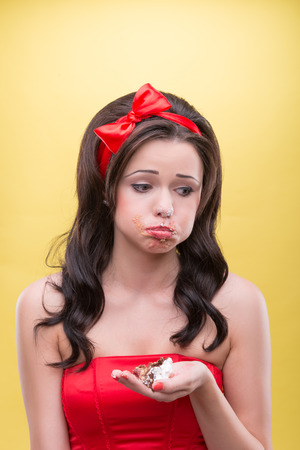 Half-length portrait of sad slovenly dark-haired girl wearing great red headband holding one little piece of her favorite dessert on her palm regretting that the cake is over  Isolated on yellow background Stock Photo - 30716767