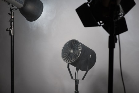 Three projectors standing enveloped in smoke  Isolated on grey background photo