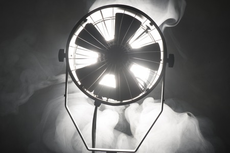 Switched cinema spotlight standing in the dark enveloped in smoke photo