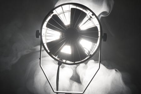 enveloped: Switched cinema spotlight standing in the dark enveloped in smoke Stock Photo