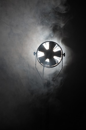 switched: Switched cinema spotlight standing in the dark enveloped in smoke Stock Photo