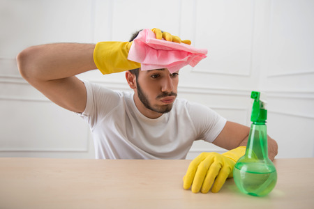 groaning: Half-length portrait of young tired dark-haired janitor wearing white shirt and yellow rubber gloves sitting at the table holding pink duster in the hand groaning