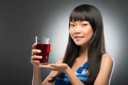 suggested: Half-length portrait of pretty young smiling dark-haired Asian woman suggested us her favorite cherry juice  Isolated on black background