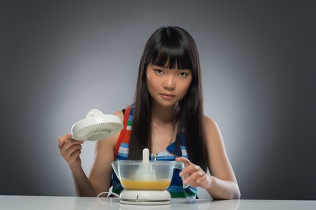 Half-length portrait of very serious young dark-haired Asian woman sitting at the table holding the important part of juicer  Isolated on black background photo
