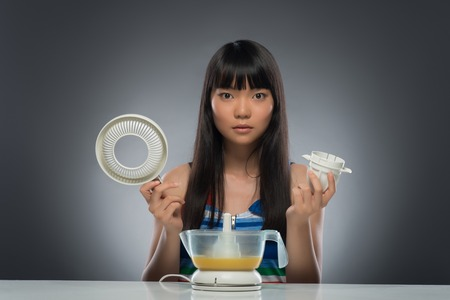 Half-length portrait of very serious young dark-haired Asian woman sitting at the table holding in both her hands two parts of juicer knowing nothing about them  Isolated on black background photo